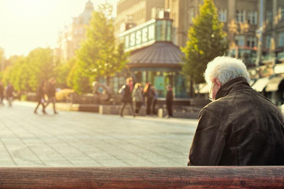 Elderly man sitting on a bench alone