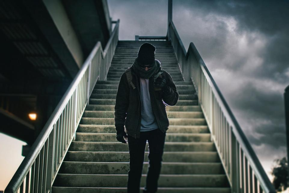 man walking down stairs with his hood up looking down